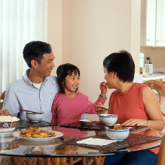 A family of Asian ethnicity sits around a table, the little girl leans against the man while handing a piece of food to the woman.