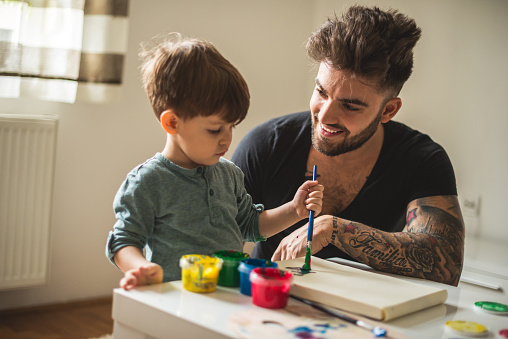 A young person with tattoos on their arm works with a child who is painting