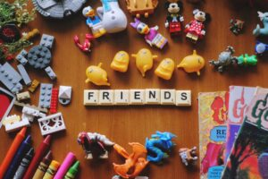 A variety of small toys are scattered over a hardwood floor, with scrabble tiles arranged in the middle to spell out the word friends